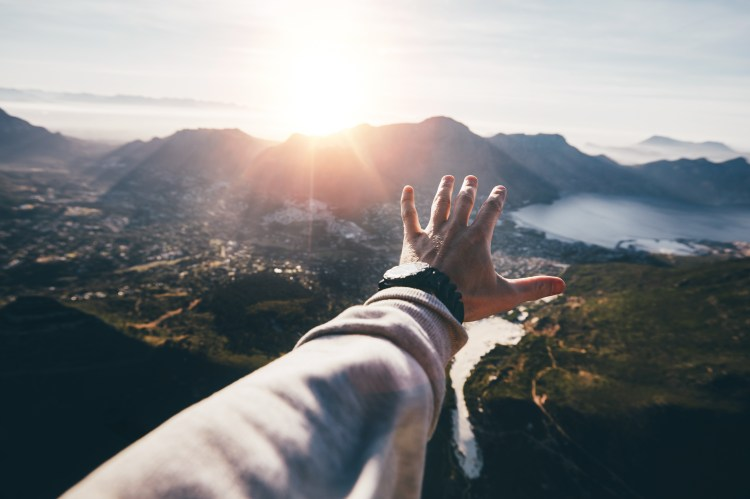 Hand of a man reaching out the beautiful landscape. POV shot of human hand on a sunny day.