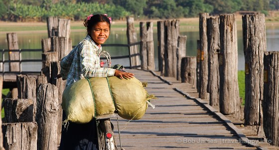 A Burmese schoolgirl looks back for a friend as she walks her bicycle across Amarapura's U Bein Bridge