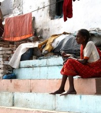 An Indian woman sits at one of Varanasi's many ghats. Photo: TravelingReporter.com