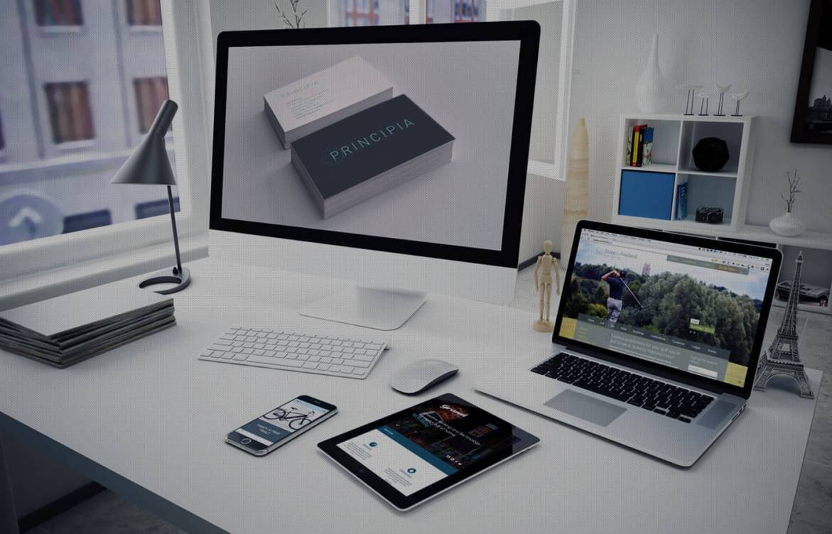A desk with a PC, laptop, tablet and smartphone displaying examples of websites and brand identities design by Tribus — Tribus Creative: Design for small business