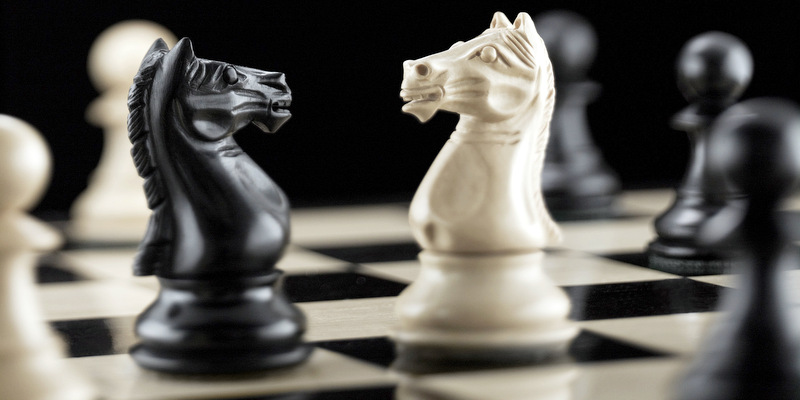 Knight chess pieces facing each other on chess board