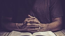 Man praying on a wooden table with an open Bible