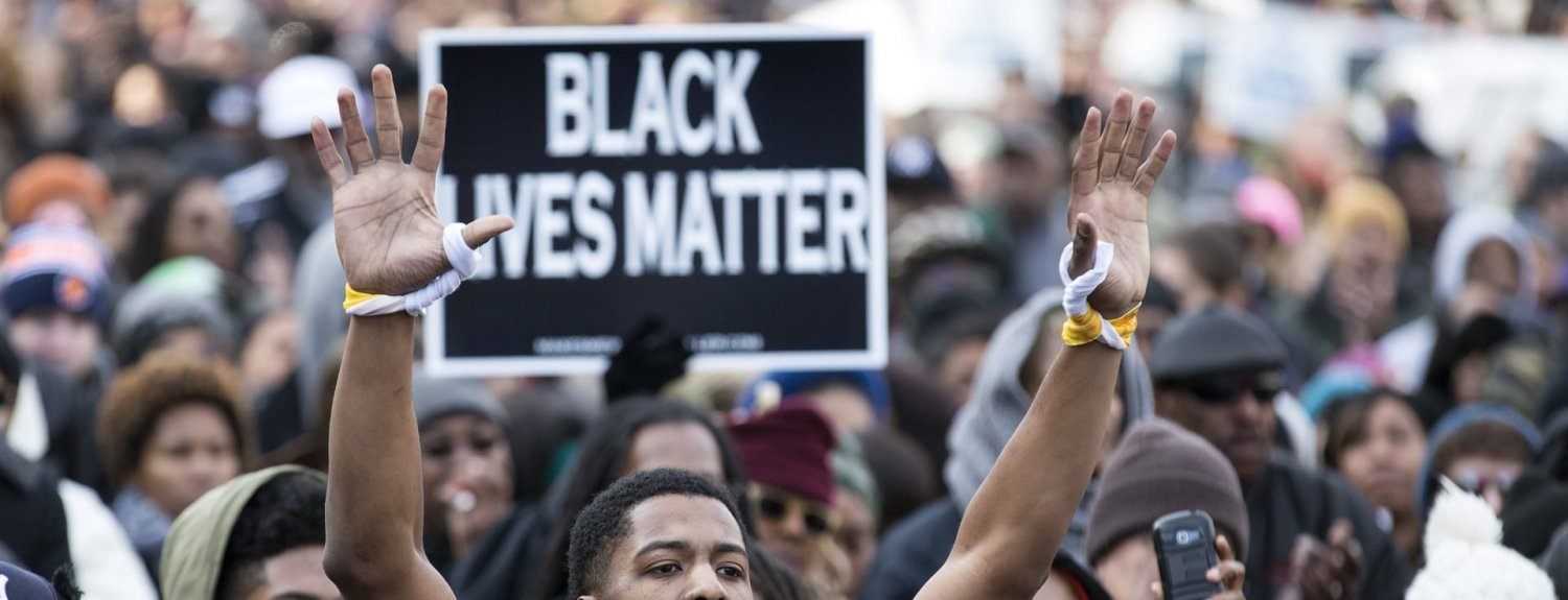 A man raises his arms at a rally during the National Action Network National March Against Police Violence in Washington December 13, 2014. Thousands of demonstrators gathered in Washington on Saturday for a march to protest the killings of unarmed black men by law enforcement officers and to urge Congress to do more to protect African-Americans from unjustified police violence.    REUTERS/Joshua Roberts    (UNITED STATES - Tags: POLITICS CRIME LAW CIVIL UNREST) - RTR4HWG2