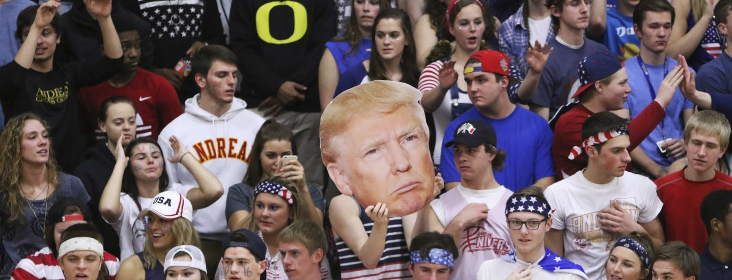 """In this Friday, Feb. 26, 2016 photo, the Andrean High School student section holds up a picture of GOP presidential candidate Donald Trump during their school's basketball game against Bishop Noll Institute in Merrillville, Ind. The Catholic bishop in northern Indiana denounced the students who waved the picture of Trump and shouted """"build a wall"""" at their opponents, a heavily Hispanic school in nearby Hammond. (Jonathan Miano/The Times via AP)  CHICAGO LOCALS OUT; GARY OUT; MANDATORY CREDIT"""
