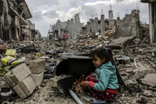 Kurdish Syrian girls are pictured among destroyed buildings in the Syrian Kurdish town of Kobane, also known as Ain al-Arab, on March 22, 2015. AFP PHOTO/YASIN AKGUL (Photo credit should read YASIN AKGUL/AFP/Getty Images)