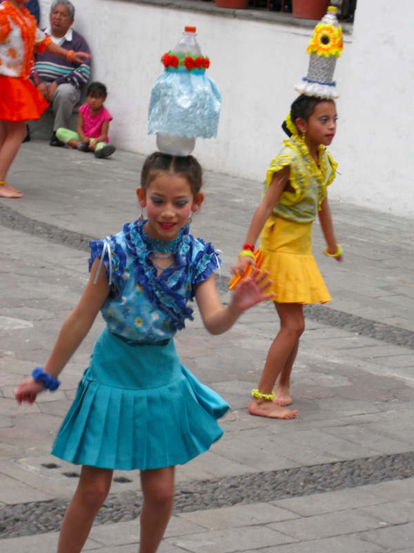 One day in Quito, I ran into an exhibition of folk dancing in the central patio of the Archbishop's Palace in the Plaza Grande. There were several groups, but the one that intrigued me most was the troupe of young girls who centered their dance around gayly decorated large plastic soda bottles which they balanced on their heads and hands as they happily spun around.
