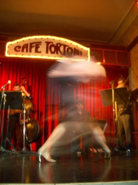 I've included a link to a photo I took in Buenos Aires at the Cafe Tortoni of two tango dancers during a show. My shutter was too slow to catch the dancers' photo, but it caught their feet and embrace as they spun wildly across the stage. I loved that they didn't come out because it helped capture the crazy passion and frenzy of the dance.
