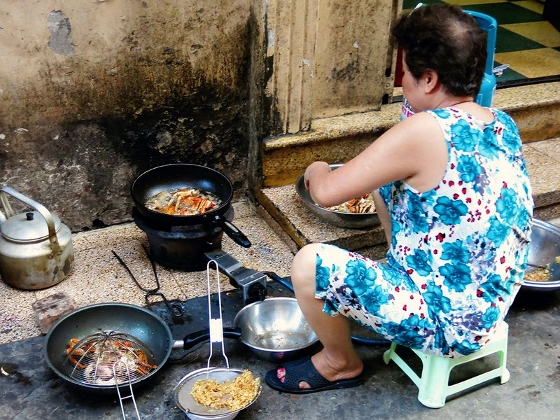 A local Vietnamese lady cooking up a storm right on the sidewalk of a busy street in Hanoi!