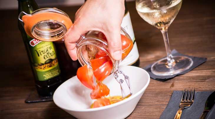 Los tomates en aceite con cebolla roja son ideales para empezar una comida en Tingana
