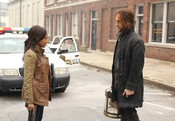 Abbie (Nicole Beharie) and Ichabod Crane (Tom Mison) gaze at each other in front of a police car as he holds the Headless Horseman's skull on the Sleepy Hollow pilot