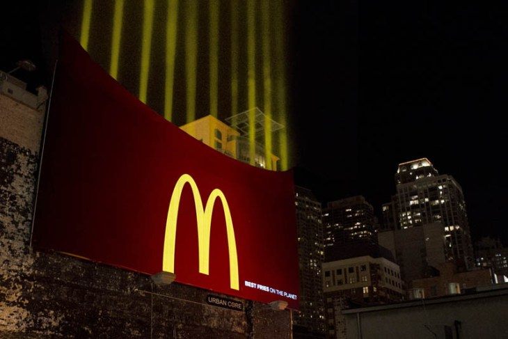 mcdonalds billboard shows fries box with lights shining upwards like french fries