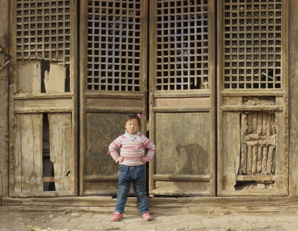 A child standing in front of a temple in the northern barbican of Wangliangzhuang Village, near Yu Xian