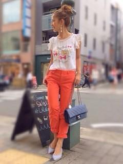 9オレンジパンツ×白プリントTシャツ×ブランドショルダーバッグ
