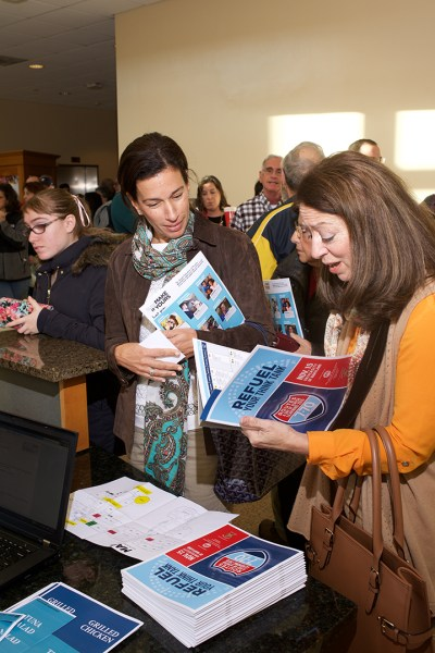 At check-in, attendees browse pamphlets describing the 70 learning sessions offered during the day-long Jewish learning event in Van Munching Hall. Courtesy of Jewish Federation of Greater Washington.