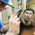 """Barber Rob Ferrel known as """"Rob the Original"""" cuts the likeness of Argentine soccer player Lionel Messi on the head of customer at his barbershop in San Antonio"""