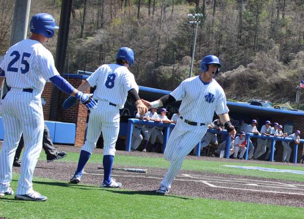 Michael Gouge celebrates with teammates Connor Hoover (8) and Conner Corbitt (25) after scoring a run against Montevallo. (Photo by Jake Cantrell)