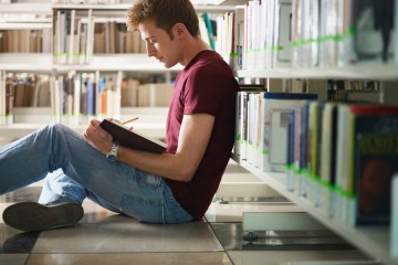 male college student sitting on floor in library, reading book. Horizontal shape, side view, three quarter length, copy space