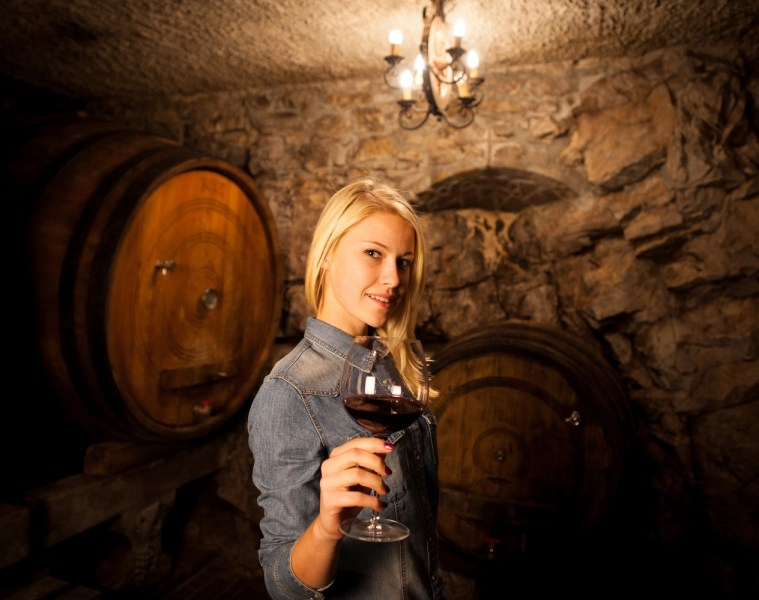 Beautiful young woman tasting red wine in a wine cellar