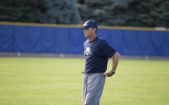 Coach Mike Littlewood coaching baseball players during practice.