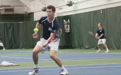 Francis Sargeant (left) returns a shot during a tennis match. Photo by Chris Bunker.