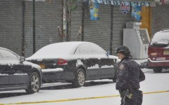 Police stand guard in an area marked with yellow tape Tuesday, Jan. 6, 2015, where police and suspects exchanged gunfire Monday, in New York. A manhunt was under way Tuesday for at least two suspects who shot and wounded two New York City plainclothes police officers responding to a robbery in the Bronx. (AP Photo/Bebeto Matthews)