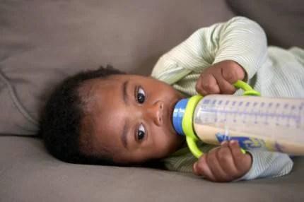 baby feeding himself a bottle of milk