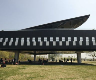 Visitors gather in front of and below a piano-shaped building in Huainan