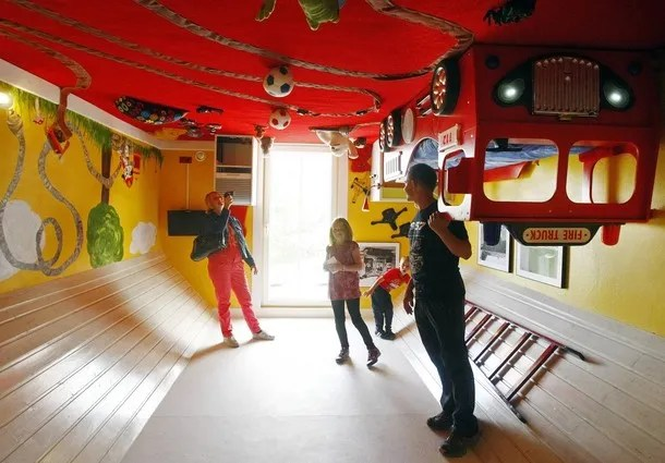 People stand inside a room of a house, which was built upside down by Polish architects Irek Glowacki and Marek Rozhanski, in the western Austrian village of Terfens May 5, 2012. The project is meant to serve as a new tourist attraction in the area, and is now open for public viewing. Picture taken May 5, 2012. REUTERS/Dominic Ebenbichler