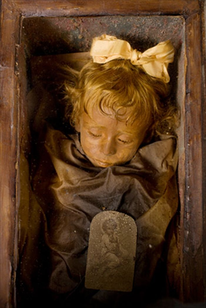 """Rosalia Lombardo, a two-year-old Sicilian girl who died of pneumonia in 1920. """"Sleeping Beauty,"""" as she's known, appears to be merely dozing beneath the glass front of her coffin in the Capuchin Catacombs of Palermo, Italy. nationalgeographic.com"""