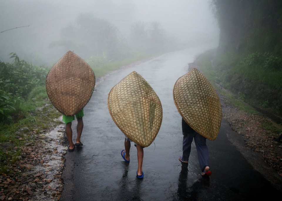 Three laborers walk into Mawsynram under the traditional Khasi umbrellas known as knups. Made from bamboo and banana leaf, the knups are favored for allowing two-handed work, and for being able to stand up to the high winds which lash the region during heavy rainstorms. (© Amos Chapple)