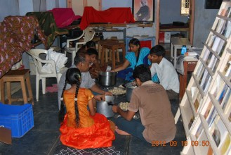 Youth and children actively participating in laddu making.