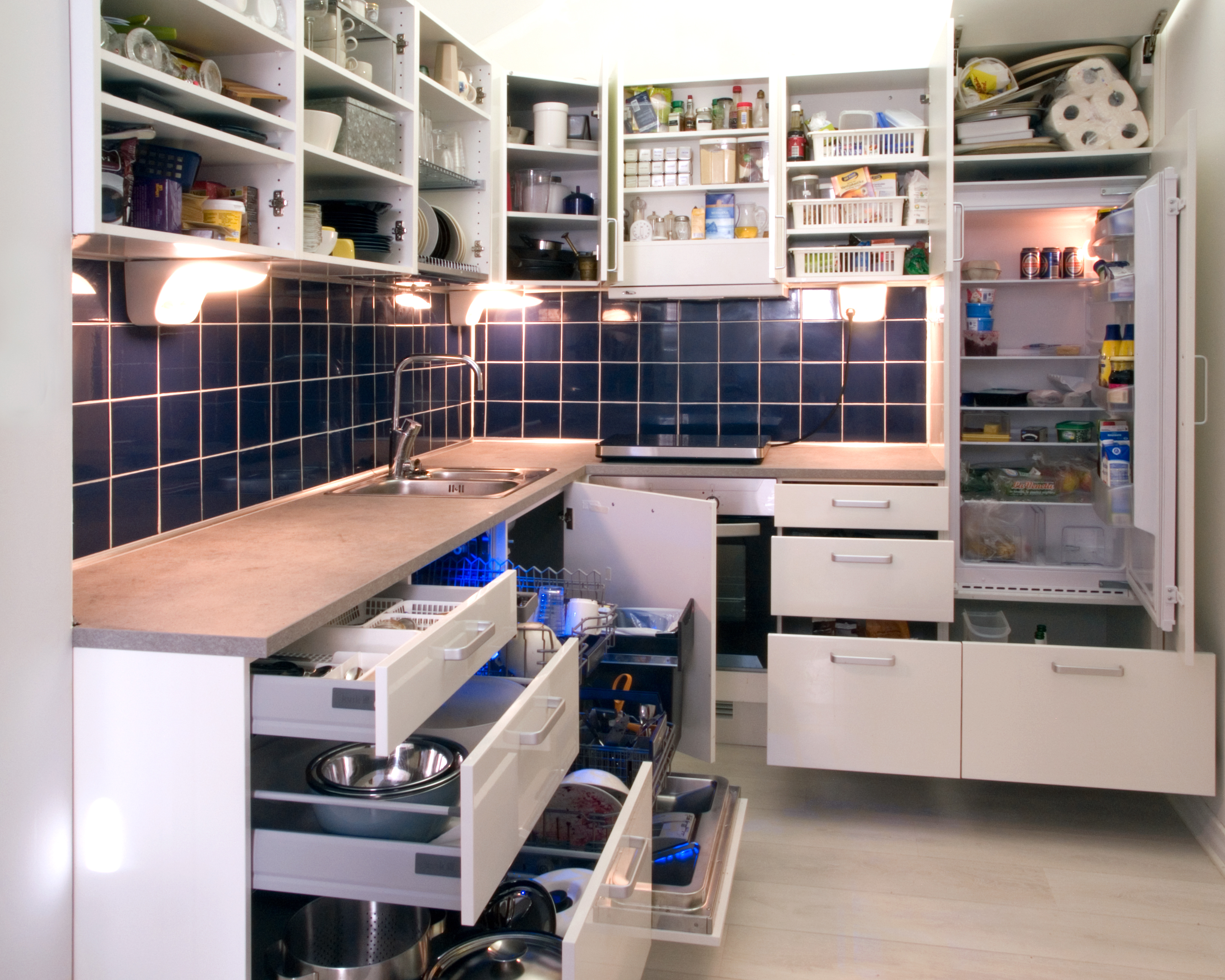 White kitchen with cabinet doors and drawers opened or removed so that real life stuff can be seen in cabinets