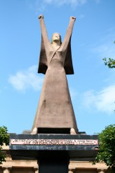 "Statue of a woman in a strong pose with both arms up in protest with fists clenched and quotation beneath ""It is better to die on your feet than to live forever on your knees."""