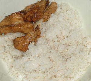 English: Filipino chicken adobo with rice.