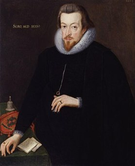 "A three-quarter portrait of a white man, dressed entirely in black with a white lace ruff. He has brown hair, a short beard, and a neutral expression. His left hand cradles a necklace he is wearing. His right hand rests on the corner of a desk, upon which are notes, a bell, and a cloth carrying a crest. Latin text on the painting reads ""Sero, Sed, Serio""."