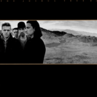 "A landscape monochrome photograph of U2 in the desert sits in the center of a black background. U2 are standing on the left half of the photograph, with a mountain range on the right half. Tiny gold text reading ""THE JOSHUA TREE U2"" is stretched across the top of the black background."