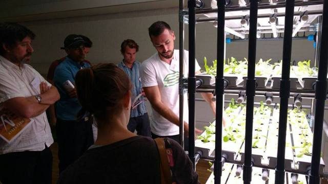 Henry demonstrating vertical hydroponic agriculture to participants in the Agritecture design workshop in London (June, 2016)