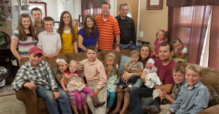The Duggar family in a 2013 file photo, with Josh and Anna, the adults on the right, showing off new baby Marcus. (TLC)