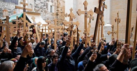Christian tourists, pilgrims and clergy held crosses as they walked outside the Church of the Holy Sepulchre during a Good Friday procession to commemorate Jesus Christ's crucifixion, in Jerusalem on April 10. (ABIR SULTAN/EUROPEAN PRESSPHOTO AGENCY)