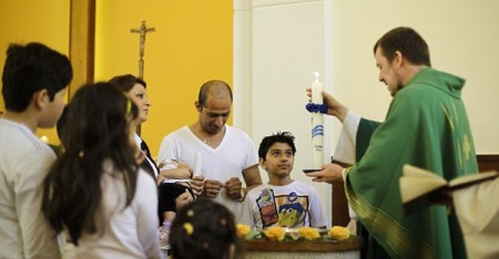 Pastor Gottfried Martens lights a candle during a service to baptise migrants from Iran at the Trinity Church in Berlin. Pictured third right is Mohammed Ali Zanoobi who is among hundreds of mostly Iranian and Afghan asylum seekers who have converted to Christianity at the evangelical church in a leafy Berlin neighbourhood. (AP)