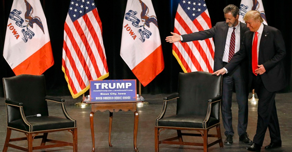 Liberty University President Jerry Falwell Jr. guides Donald Trump to his chair at a campaign event in Iowa in January 2016. (Patrick Semansky / AP)