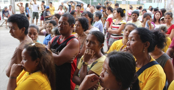 People wait for relief goods outside a Catholic church after evacuating their homes due to super-typhoon Hagupit in the Philippines in December 2014. Tens of thousands of people fled coastal villages and landslide-prone areas in the central Philippines. (Reuters)