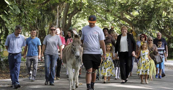 Members of the Coral Gables Congregational Church of Christ, and Jeremiah the donkey, meet on April 9 at Salvadore Park for a parade to celebrate Palm Sunday Services in preparation for Easter Sunday. (C.M. Guerrero/El Nuevo Herald via AP)