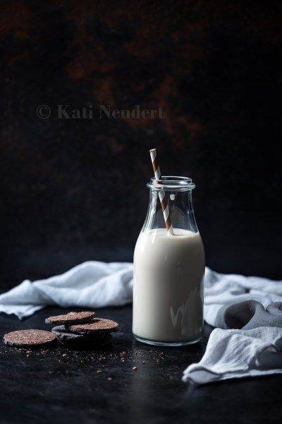 Vegane Hafer-Kekse und Flasche mit Haferdrink.