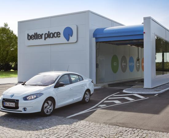 A Renault Fluence ZE electric car exits a Better Place battery switching station.