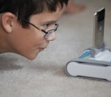 A child stares at a dimunitive Romo, an iOS-powered robot.