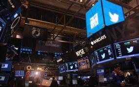 Journalists rush across the stock exchange floor.