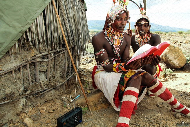 Masai tribesman reads a book.