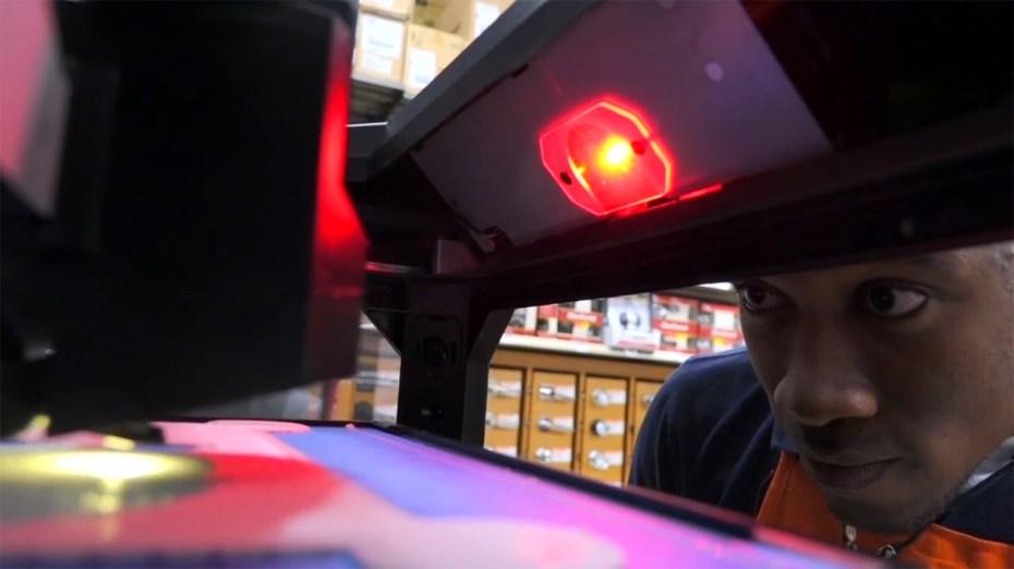 A Home Depot employee looks inside a MakerBot 3D printer.