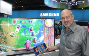 Playsino CEO Alex Kelly in front of Bingo Home on a big Samsung TV at CES 2015.